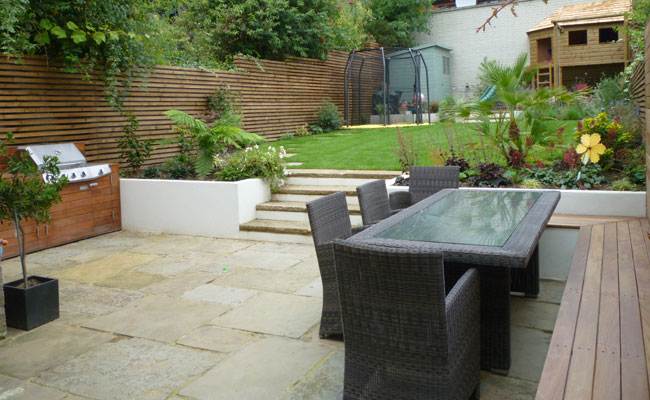 Paved Patio Area With Bench Seating Leading To The Lawn.