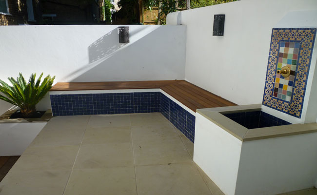 Landscape gardeners, North London design patio and garden bench with water feature.